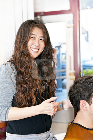 Hairstylist working stock photo, Smiling hairdresser cutting hair in her salon by Elena Elisseeva