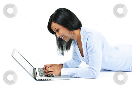 Young woman using laptop computer stock photo, Smiling black woman typing on computer laying on floor by Elena Elisseeva