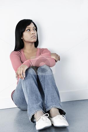 Depressed woman sitting on floor stock photo, Depressed black woman sitting against wall on floor looking away by Elena Elisseeva