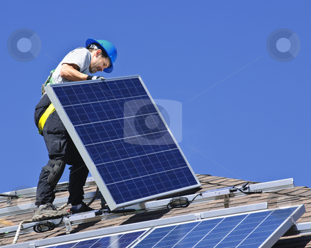 Solar panel installation stock photo, Man installing alternative energy photovoltaic solar panels on roof by Elena Elisseeva