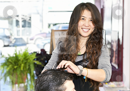 Hairstylist working stock photo, Happy hairdresser cutting hair in her salon by Elena Elisseeva