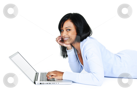 Pretty young woman with computer stock photo, Smiling black woman using computer laying on floor looking at camera by Elena Elisseeva