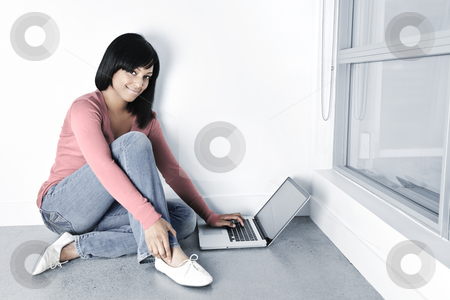Young woman using laptop computer on floor stock photo, Young black woman with laptop computer sitting on floor smiling by Elena Elisseeva