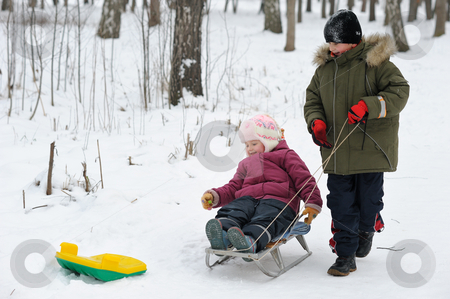 Winter Games Children stock photo, Winter games children - a girl on a sledge and a boy next. by Vladimir Blinov