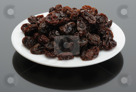 Raisin on a white plate on a black background stock photo, Big brown raisins on a white plate on a black background by Vladimir Blinov