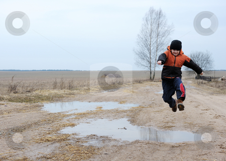 Jumping boy stock photo, A boy jumps over a puddle on a rural road by Vladimir Blinov