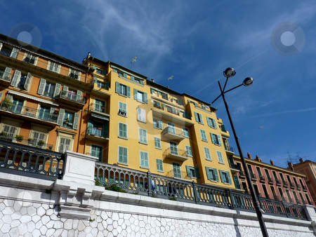 Colored buildings and birds stock photo, Three birds flying next to beautiful colored buildings in Nice, old port, France by Elenaphotos21