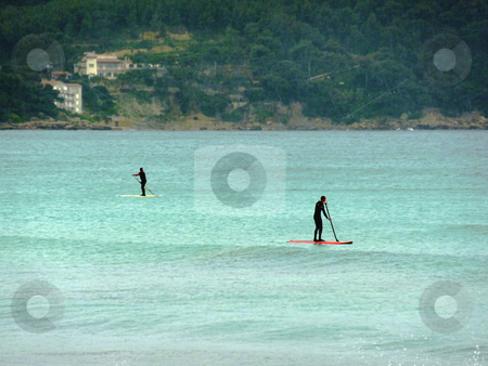 Surfers on the sea stock photo, Two suited surfers with paddles on the mediterranean coastline by Elenarts