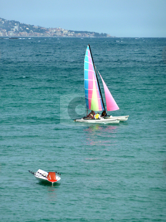 Very colored sailing boat stock photo, Colorful sailing boat with many people inside and a small white boat floating on the mediterranean sea near the coastline by beautiful weather by Elenaphotos21