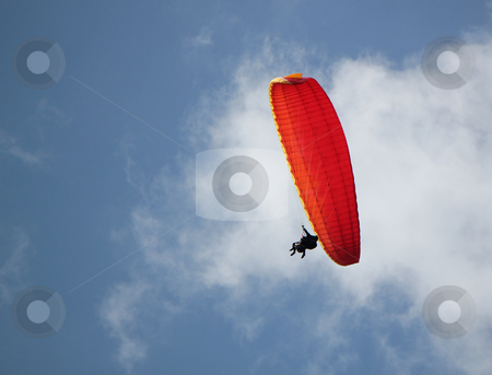 Red paraglider stock photo, Man flying in the cloudy sky with its red paragliding by Elenaphotos21