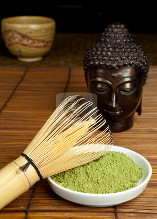 Zen tea stock photo, Zen image of a bronze buddha and japanese green tea by Anneke