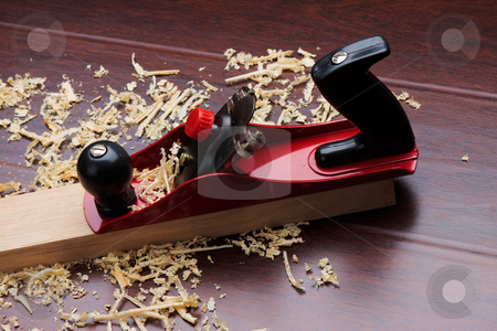 Red plane on brick and shavings. stock photo, Red plane on brick and shavings on the floor. by Andrey Lipko