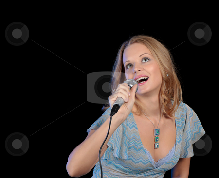 Portrait of the young beautiful girl singing in a microphone stock photo, Portrait of the young beautiful girl singing in a microphone. by Andrey Lipko