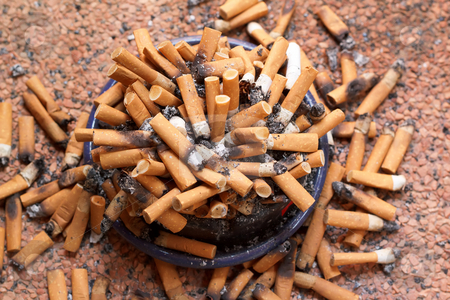 Ashtray full of cigarettes close-up stock photo, Ashtray full of cigarettes close-up by Artush