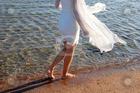 Walking by sea on sand stock photo, Woman in white dress back and legs walking by sea on sand by Julija Sapic