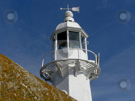 Mevagissey Light House  stock photo, A bright white lighthouse, peeking up above the pier at Mevagissey, Cornwall, England. by Mary Lane