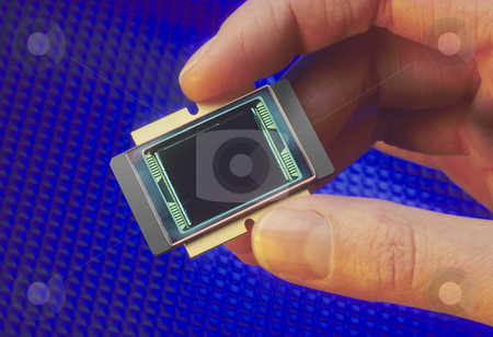 Microprocessor chip stock photo, Fingers holding a microprocessor chip on blue background by Christian Delbert