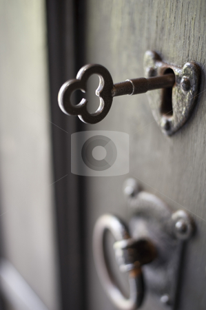 Old locked door stock photo, An old door handle and lock with a key in it, pictured with a narrow depth of focus by Stephen Gibson