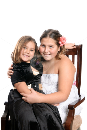 Happy Sisters stock photo, Two happy sisters are sitting on a wooden chair, isolated against a white background. by Richard Nelson