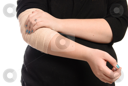 Elbow Injury stock photo, A young girl is holding her elbow which is wrapped in a tensor bandage, isolated against a white background. by Richard Nelson