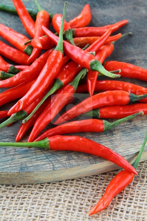 - cutcaster-photo-100917565-Red-Hot-Chili-Peppers-over-wooden-background