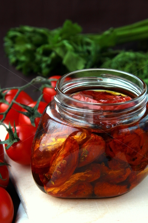 Italian sun-dried tomatoes in olive oil, glass jar stock photo,  by Olga Kriger