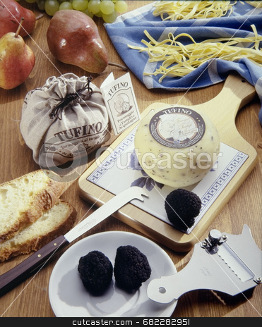 Italian cheese plate stock photo, Assortment of italian cheeses on a plate with a knife and some fruit by Luca Mosconi