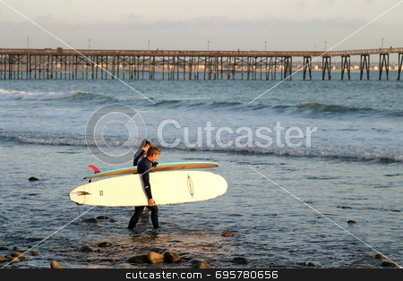 Off To Sunset Surf stock photo, Surfer at sunset at the beach near the pier in Ventura California. by Henrik Lehnerer