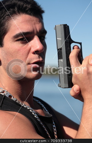 Armed 1 stock photo, A young man, wearing a sleeveless shirt, holding a hand gun. (This image is part of a series) by Daniel Wiedemann