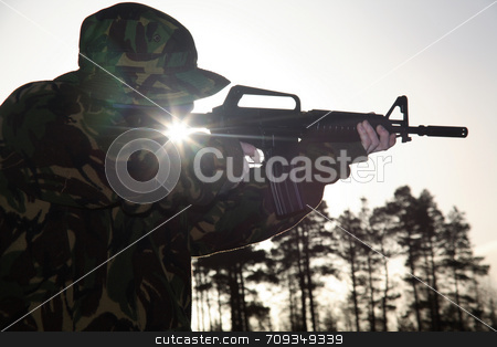 Soldier, his Rifle and the Sun stock photo, A soldier standing up pointing a rifle foward, covered with camouflage with the Sun shining through. by Daniel Wiedemann