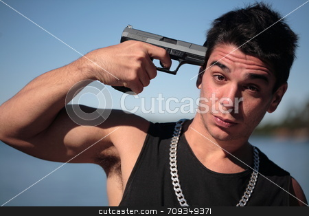 Armed 5 stock photo, A young man, wearing a sleeveless shirt, holding a hand gun. (This image is part of a series) by Daniel Wiedemann