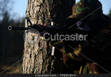 Soldier and his Rifle stock photo, A soldier behind a tree, holding a rifle. by Daniel Wiedemann