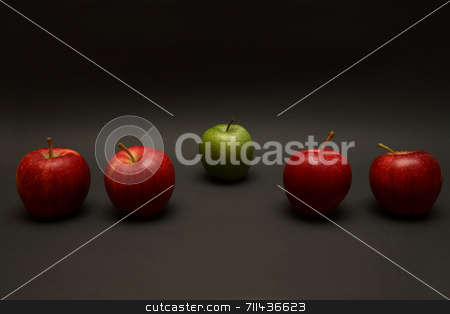 Odd One Out stock photo, A line of apples, with one red one out. by Daniel Wiedemann