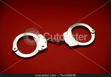 Handcuffs stock photo, A pair of closed handcuffs. by Daniel Wiedemann