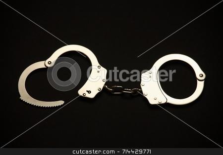 Handcuffs stock photo, A pair of open handcuffs. by Daniel Wiedemann
