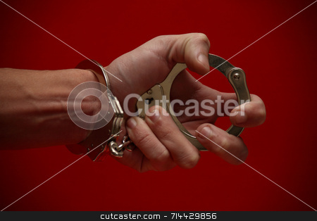 Expression stock photo, A really expressive photograph of a hand (handcuffed) holding the other end of the cuffs, on a red background! :) by Daniel Wiedemann