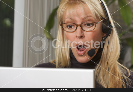 Attractive Businesswoman with Phone Headset stock photo, Attractive businesswoman galks in surprise while on her phone headset. by Andy Dean