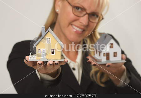 Houses in Female Hands stock photo, Female holding two houses and presenting one. by Andy Dean