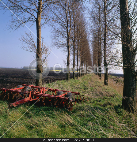 Distance stock photo, An old plough in the foreground of an avenue of trees by Paul Phillips