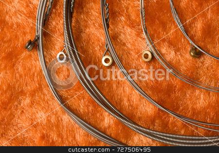 Steel guitar strings stock photo, Steel guitar strings on an orange background by Jon Stokes