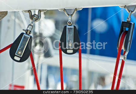 Sailing pulleys stock photo, Three pulleys and red rope on a boat by Massimiliano Leban
