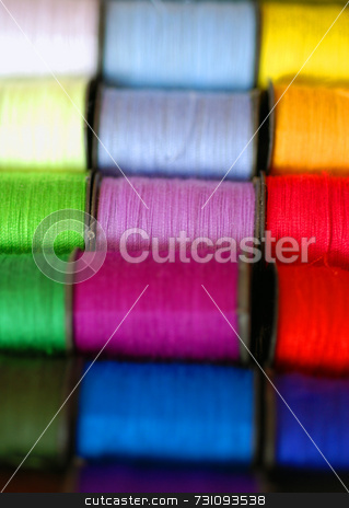 Colourful spools of cotton stock photo, A close up photograph of multi-coloured spools of cotton. by Philippa Willitts
