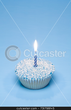 Blue cupcake with white sprinkles stock photo, A blue cupcake with white sprinkles and a candle by Jon Stokes