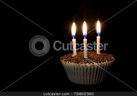 Cupcake with Candle stock photo, A cupcake with three lit candles in the dark by Jon Stokes