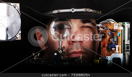 Cowboy inspects and repairs video computer component through magnifying glass stock photo,  by Chris Martin