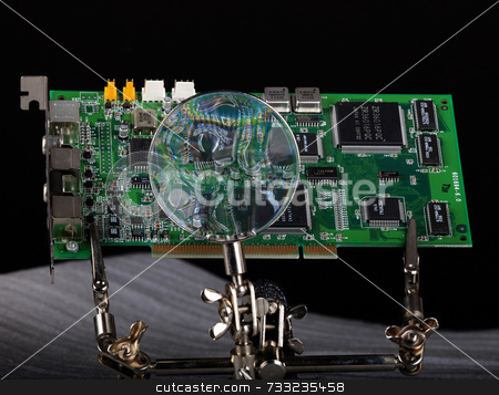 Video graphics card with circut board under magnifying glass for repair stock photo,  by Chris Martin