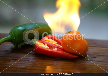 Flaming Hot Chiles stock photo, Extreamly hot peppers on fire cut open. by Lynn Bendickson