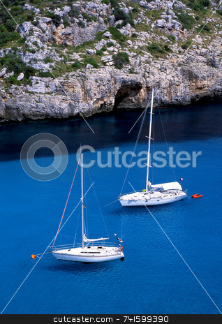 Floating stock photo, Two sailboats floating on a clear blue sea in a bay on the greek island of Corfu by Paul Phillips