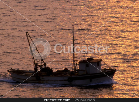 Homeward Bound stock photo, A greek fishing boat on its way home in the sunset by Paul Phillips
