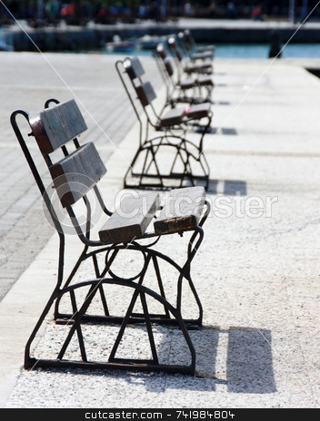 Row of Benches stock photo, A row of benches on a seafront (focus is at the front end of the first bench) by Georgios Alexandris